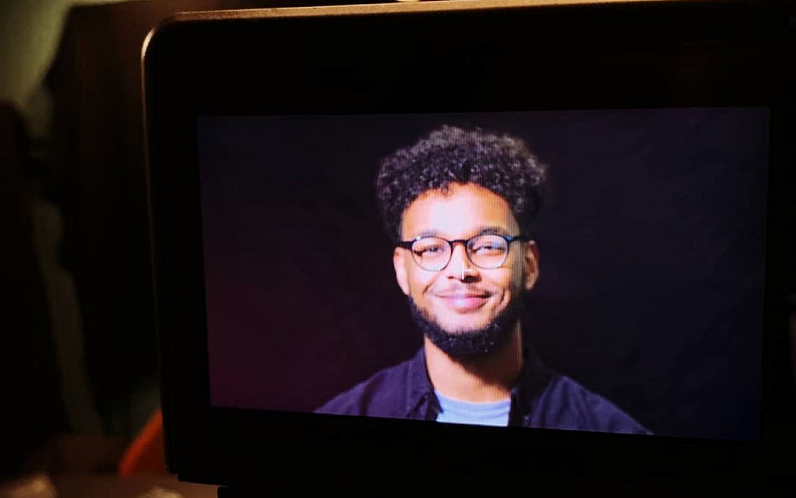 A picture of a camera where you can see Ahmed being filmed. He's got a big grin while standing in front of a black background. He's looking straight down the camera lens. He's wearing glasses and a blue t-shirt and a blue shirt,