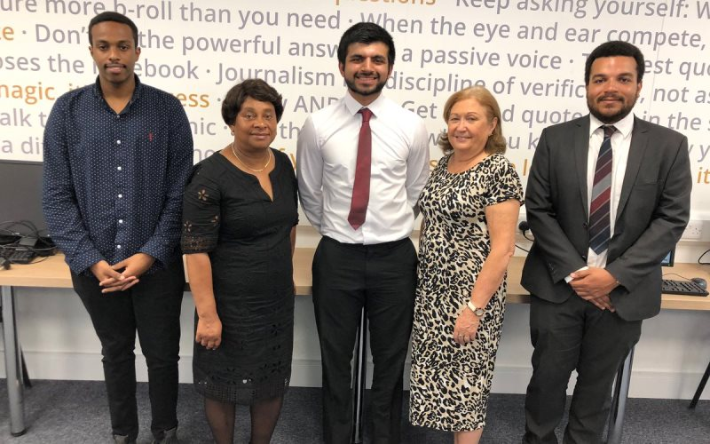 Standing in a line are Kamal Sultan wearing a blue shirt with his hands clasped in front of him, Baroness Lawrence in a smart black dress, Kumail Jaffer looking very smart in a white shirt with a red tie and a big grin, Sue Ryan wearing a leopard print dress and Courtney Bartlett looking very smart in a grey suit with a white shirt and striped tie. Baroness Lawrence and Sue Ryan are noticeably shorter than the men!