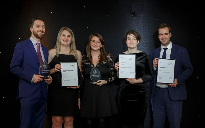 News Associates staff and trainees with their awards at the 2019 NCTJ Awards for Excellence. Graham Moody, Ella Jerman, Lucy Dyer, Jen Tombs and Cormac Connelly are standing on a stage in front of a black backdrop. They all look very smart. Lucy and Graham are holding glass awards while the trainees are holding framed certificates.
