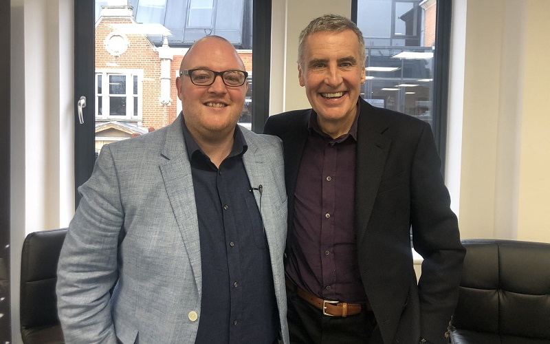 Dermot Murnaghan in a burgundy shirt and black jacket on the right standing with his arm around News Associates head of journalism Andrew Greaves in a dark blue shirt and light blue jacket. They both have big grins on their faces.