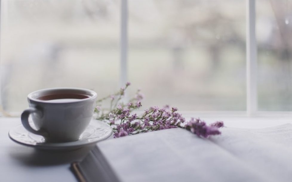 A white mug, a book and some lavender.