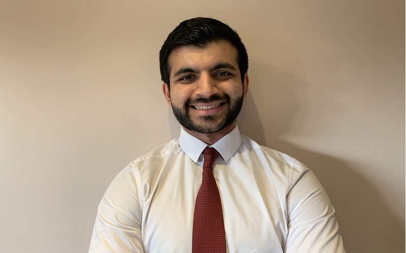 Kumail Jaffer smiling in a white shirt and red tie against a white wall