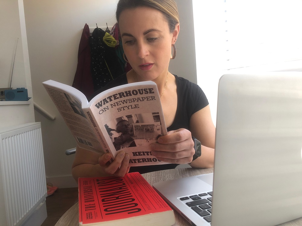 News Associates Manchester part-time trainee Gemma Corby wearing a black t-shirt with her dark blonde hair tied back and hoop earrings sitting down reading Waterhouse on Newspaper Style by Keith Waterhouse in front of a laptop