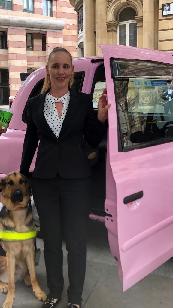 Kate Pounds with her blonde hair tied back wearing a white and black spotty blouse with a black jacket and black trousers standing next to a bright pink taxi next to her guide dog Bertie outside the Bloomberg offices.