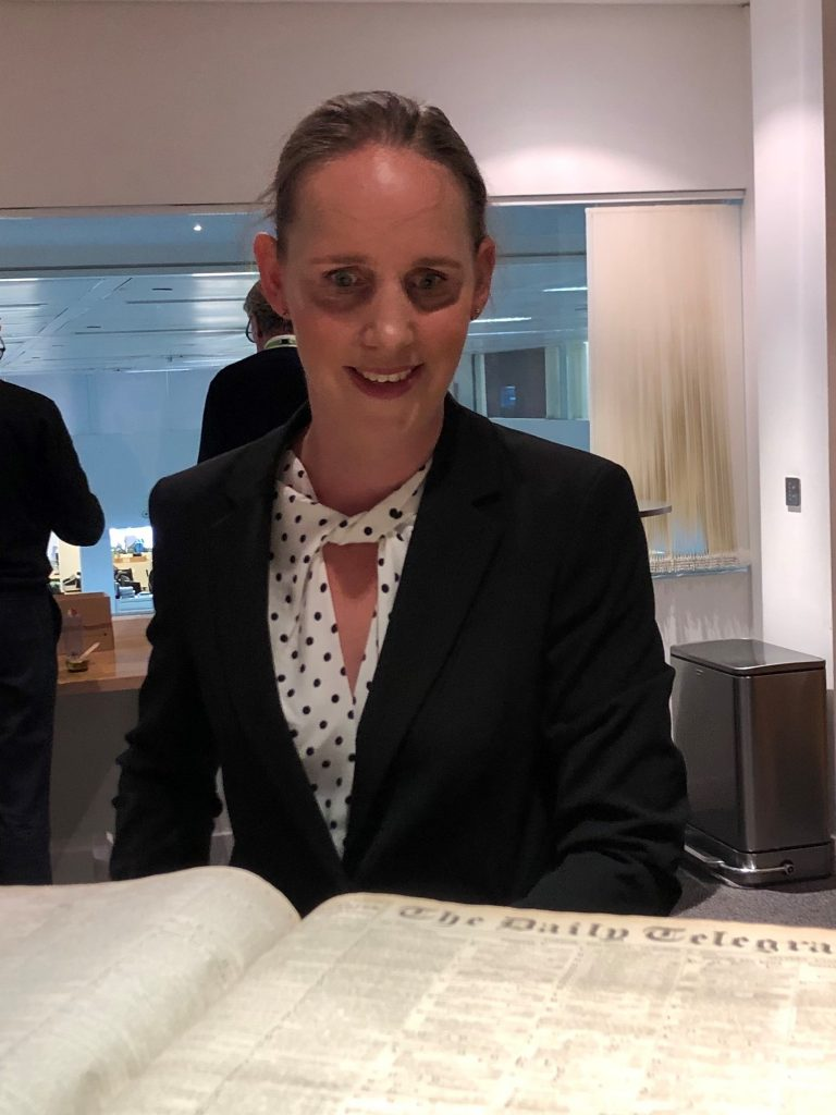 Kate Pounds with her hair tied back, wearing a white and black spotty blouse and a black jacket, looking a 100-year-old copy of The Daily Telegraph newspaper.