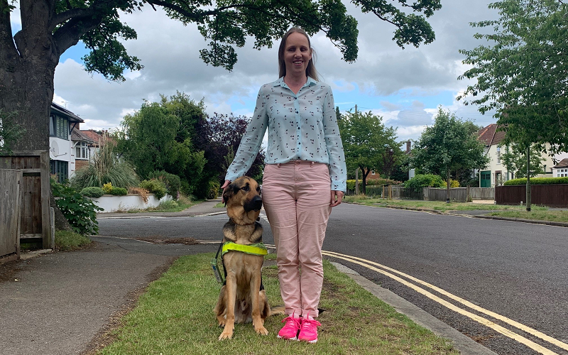 Kate Pounds and her guide dog Bertie outside on a patch of grass underneath a tree. Kate's blonde hair is down, she is wearing a blue blouse with pale pin trousers and pink trainers.