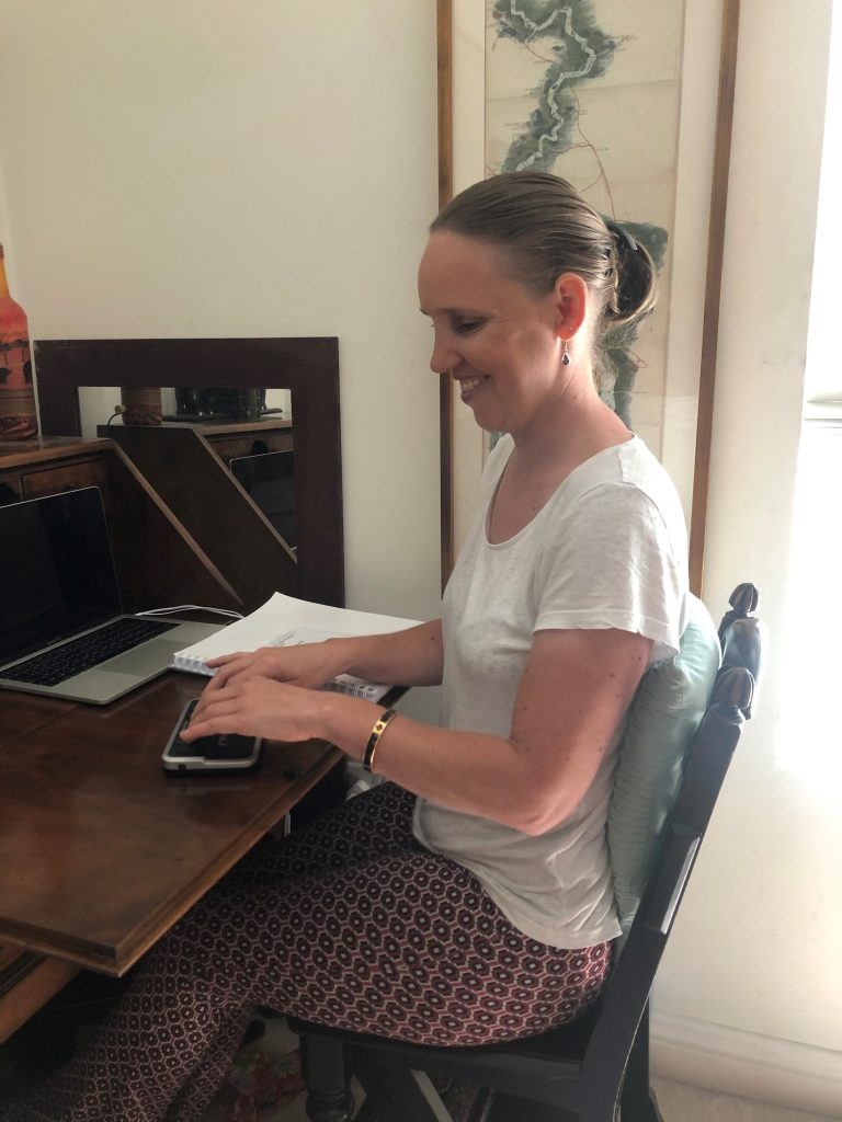 Kate Pounds looking very happy using her notetaker. She looks relaxed sitting at her mahogany desk on a mahogany chair with a green cushion behind her back. She is wearing a white t-shirt and pink patterned trousers. The notetaker is a small black device with keys. You can also see her Mac laptop and printed Braille code book on her desk.