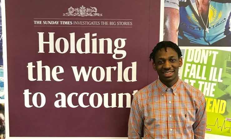 Shingi Mararike wearing an orange and blue checked shirt smiling, standing in front of a burgundy Sunday Times poster that reads 'Holding the world to account'.