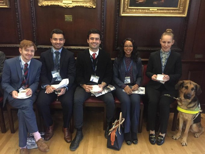 Five News Associates journalists sitting on dark wooden chairs with burgundy padding against a dark wooden wall at the Society of Editors' conference in Stationers' Hall in London. They are all very smartly dressed. Left to right are Matt Banks, Joshua Graham, Will Cracknell, Sammy Mngqosini and Kate Pounds. To the right of Kate is her guide dog Bertie.