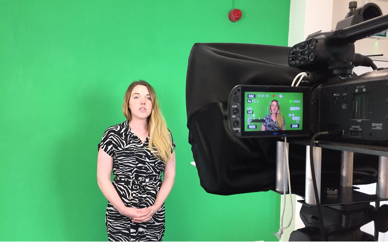 News Associates trainee Emily wearing a black and white jumpsuit presenting in front of a green screen wall being filmed by a black camera on a tripod. The image is to reflect the changes made to the diploma resulting in it becoming a level 5 qualification.