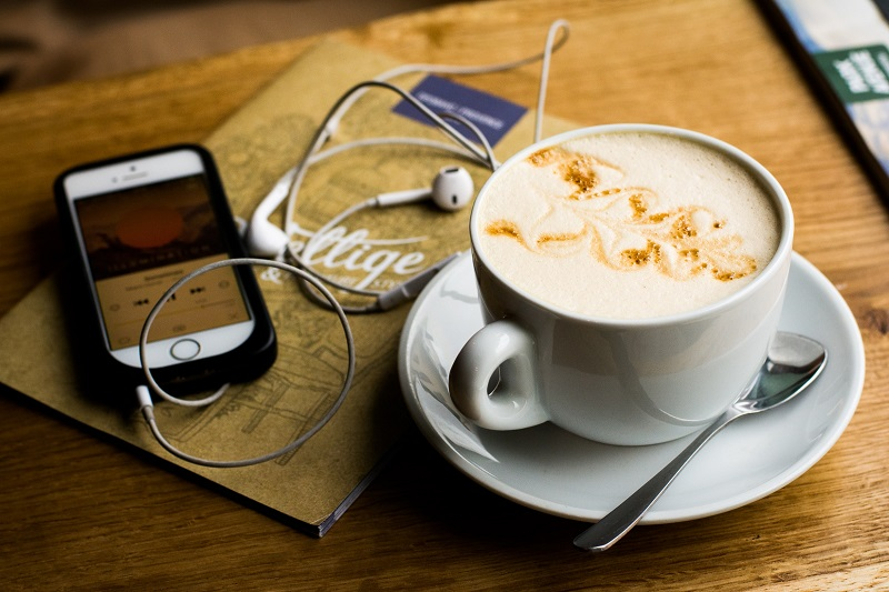 iPhone and coffee mug stock photo. White iphone is on the left, showing a podcast or song being played. White earphones are lying on top of a brown coffee shop menu, with a creamy latte in a mug on the right, sitting on a saucer with a teaspoon next to it. The objects are placed on a wooden table.