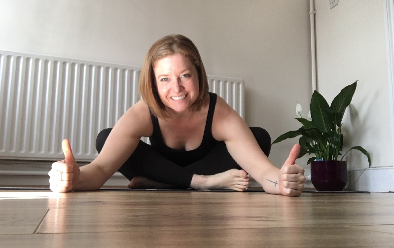 Yoga teacher Emma in a black strap top and black leggings. She is sitting at home on her wooden floor. Her legs are crossed and she is leaning forward with her arms stretched and her hands on the floor in a thumbs up. Emma has short brown and a huge grin. The white background is quite plain but to Emma's left is a luscious green leafy house plant in a dark pot.
