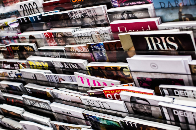 A close up of a packed magazine rack. The magazines are a variety of colours and are lined up next to and above each other. We are using it to illustrate our article about the best places to pitch to as an aspiring journalist,