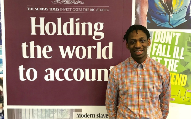 "NCTJ-accredited journalist Shingi is standing in front of a Sunday Times banner which reads ""Holding the world to account"""