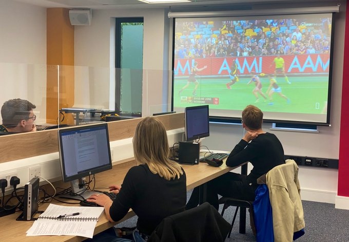 Three trainees sat socially distanced with a Perspex screen splitting the desk sitting in front of computers watching a screen showing Aussie Rules football.