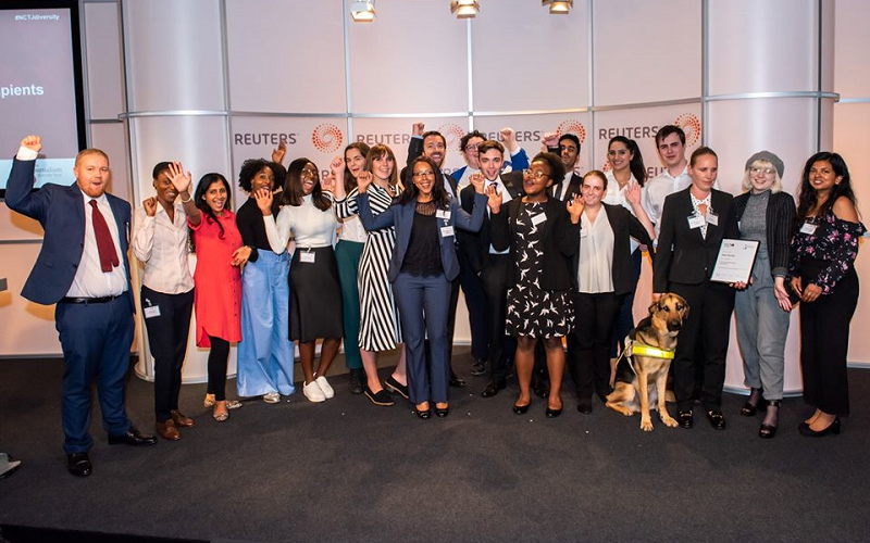 19 News Associates trainees and recipients of the Journalism Diversity Fund and our head of journalism Graham Moody at a JDF event at Reuters in 2019. Everyone is standing in a row, all dressed smart, cheering and smiling, many with their arms in the air. They are standing in front of a white wall with the black and orange Reuters loge printed on it.