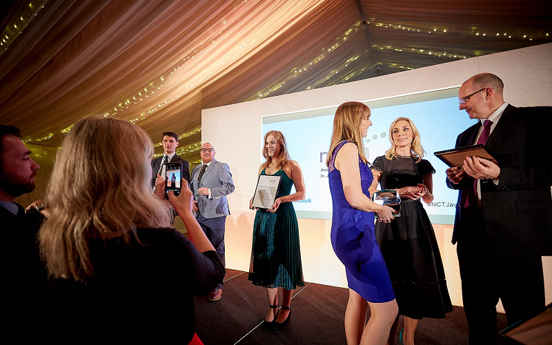 A candid shot of people on stage at the NCTJ Awards for Excellence in 2018. You can see graduate Jess Cripps in a beautiful emerald green sparkly dress posing for a picture holding her framed certificate which her mum is taking on an iphone which you can also see in shot. Other people, including head of journalism Andrew Greaves, are milling around.