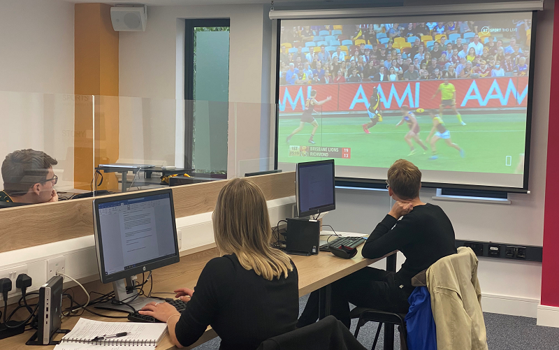 Three trainees on our journalism courses sat socially distanced with a Perspex screen splitting the desk sitting in front of computers watching a screen showing Aussie Rules football.