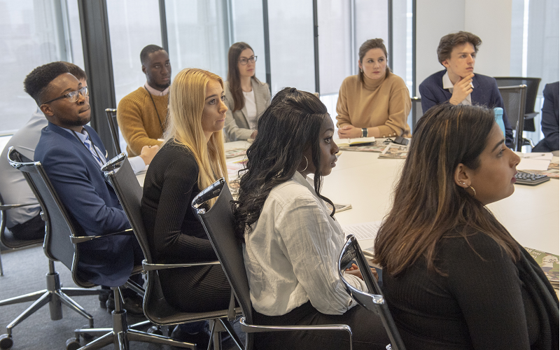 A group of News Associates/News UK trainees sitting around a large round table at News UK. You can see nine young journalists all dressed smartly looking at someone who is out of shot.