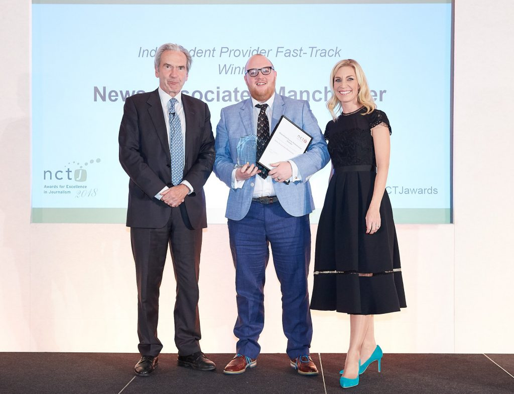 Andrew Greaves collecting the award for top NCTJ journalism school and fast-track course in 2018. He's standing with NCTJ chairman Kim Fletcher and Sky News presenter Sarah Hewson. They're all dressed up very smart with big smiles.