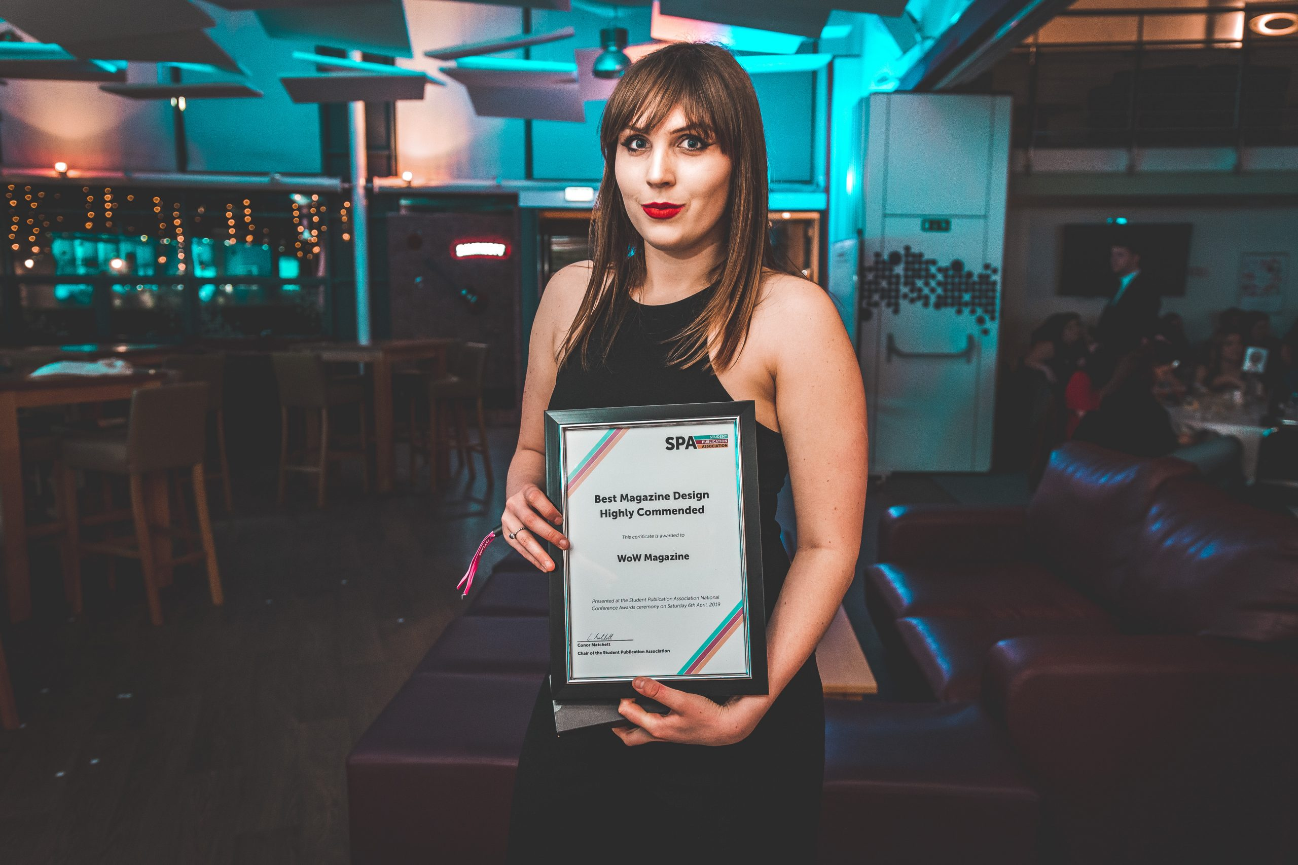 News Associates alumna Alice collecting with her award at the SPA National Conference in 2019. She's holding her framed certificate posing at the camera. She's wearing a formal black dress, her brown hair is straight and she's wearing red lipstick.
