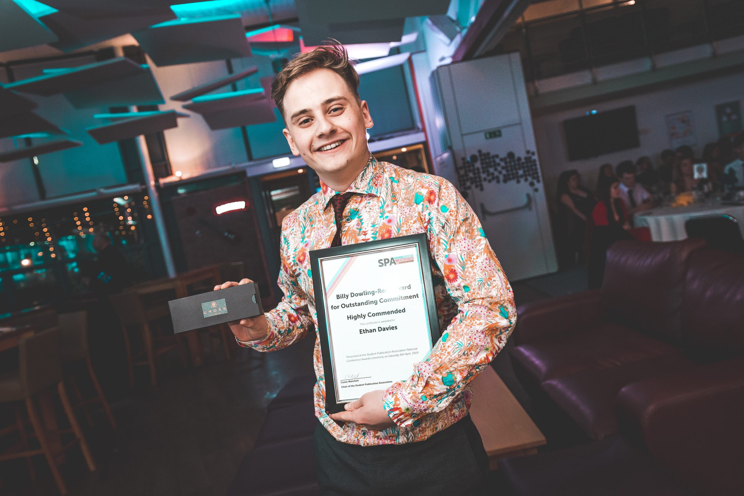News Associates alumni Ethan with her award at the SPA National Conference in 2019. 2019. He's holding her framed certificate posing at the camera. He's wearing a very jazzy orange and turquoise floral shirt and has a huge grin.