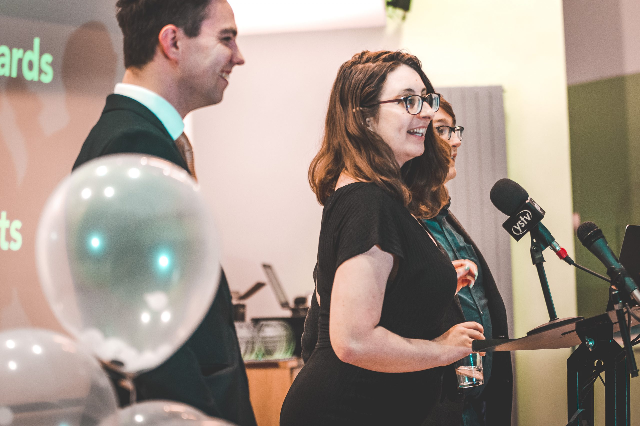 Jem Collins presenting an award at the SPA National Conference in 2019. It's a side angle as she talks into a microphone on a podium. She's dressed in all black and her dark brown hair is down. She's wearing glasses and holding a glass of water. She's smiling but it's a candid shot.