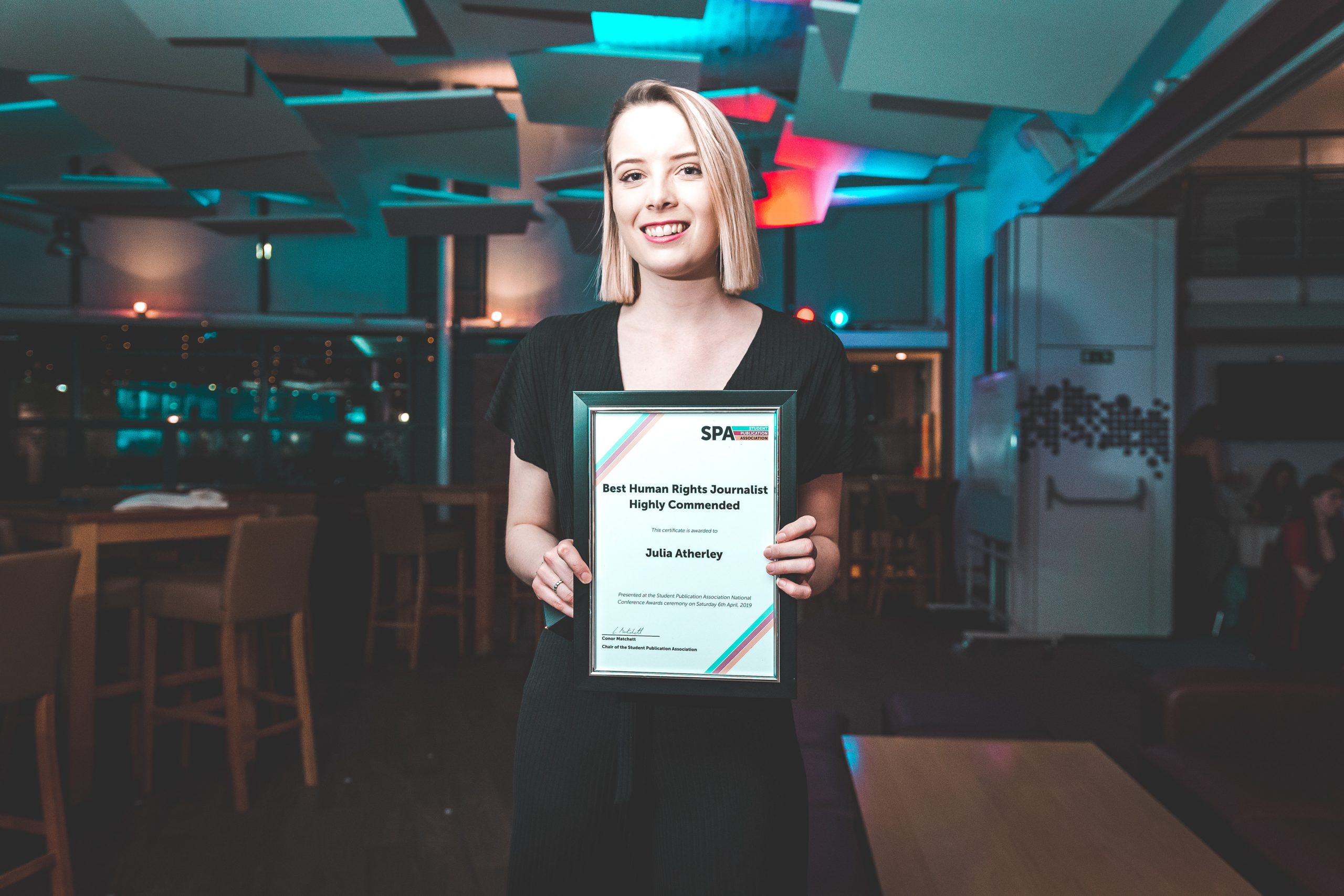 News Associates alumna Julia with her award at the SPA National Conference in 2019. 2019. She's holding her framed certificate posing at the camera. She's wearing a formal black dress, her blonde hair is straight and she's smiling.
