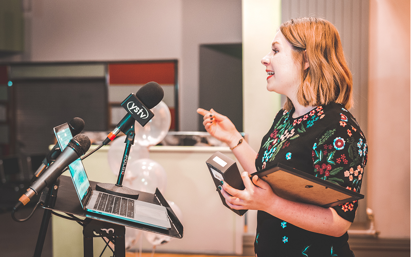 News Associates alumna Liv collecting an award at SPANC 2019. It's a side angle as she talks into a microphone on a podium. She's wearing a black dress with colourful embroidered flowers.