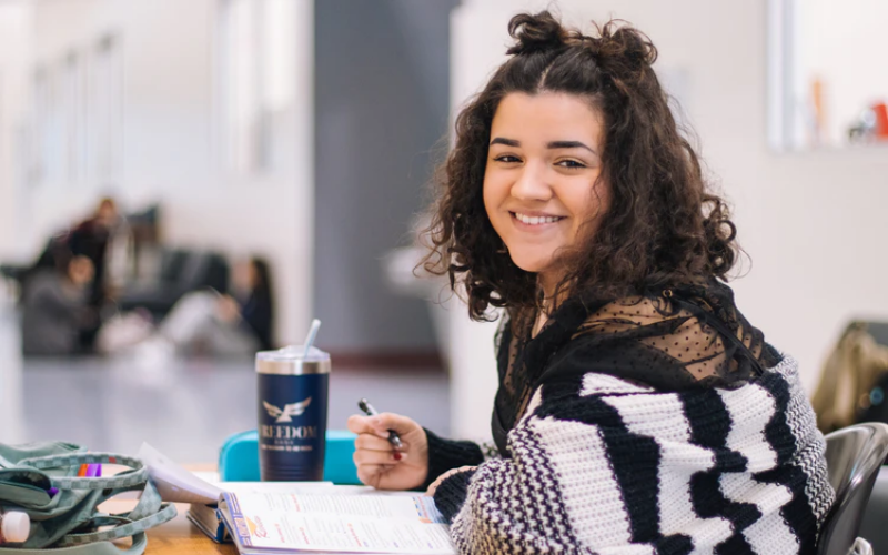 Stock image of girl working at a desk. Facing the camera smiling with short, curly brown hair. Wearing stripy jumper with pen in right hand.