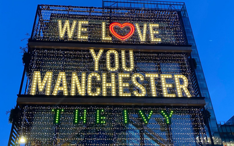 Photo of We Love You Manchester sign outside the Ivy, lit up with a loveheart replace the o in love